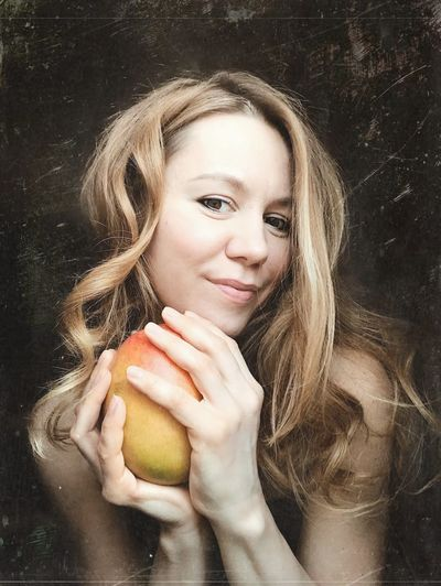 Portrait of a smiling young woman holding apple