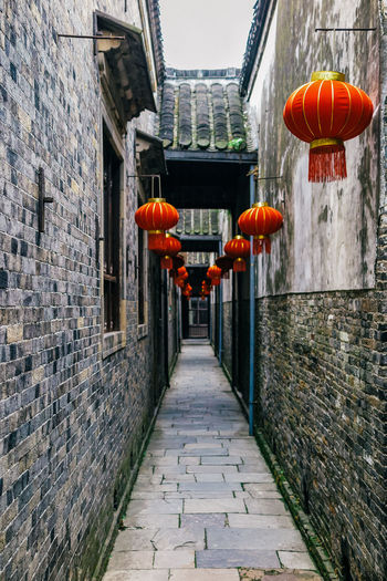 Lanterns hanging in alley against sky