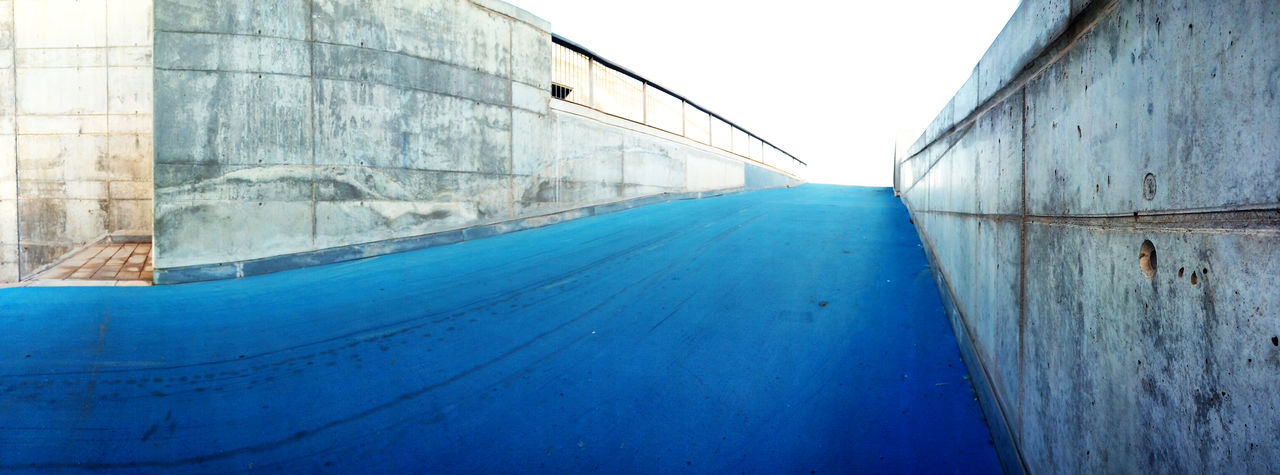 Panoramic Shot Of Empty Road By Building Against Sky