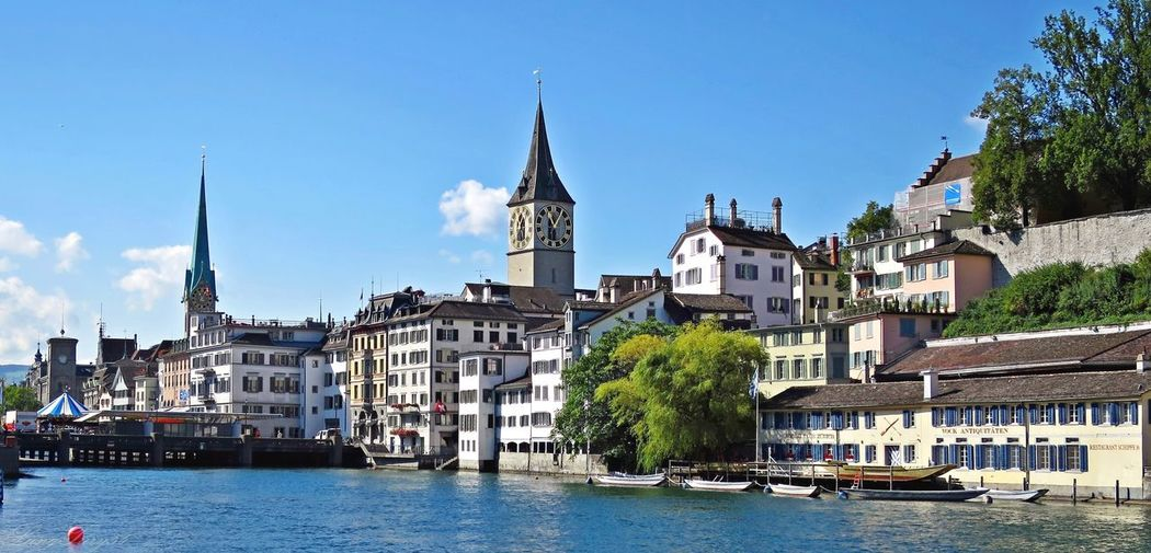 Churches and buildings by limmat river in city against blue sky