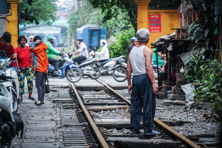Rear view of people walking on railroad tracks