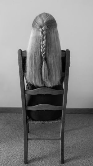 Rear view of woman sitting on chair