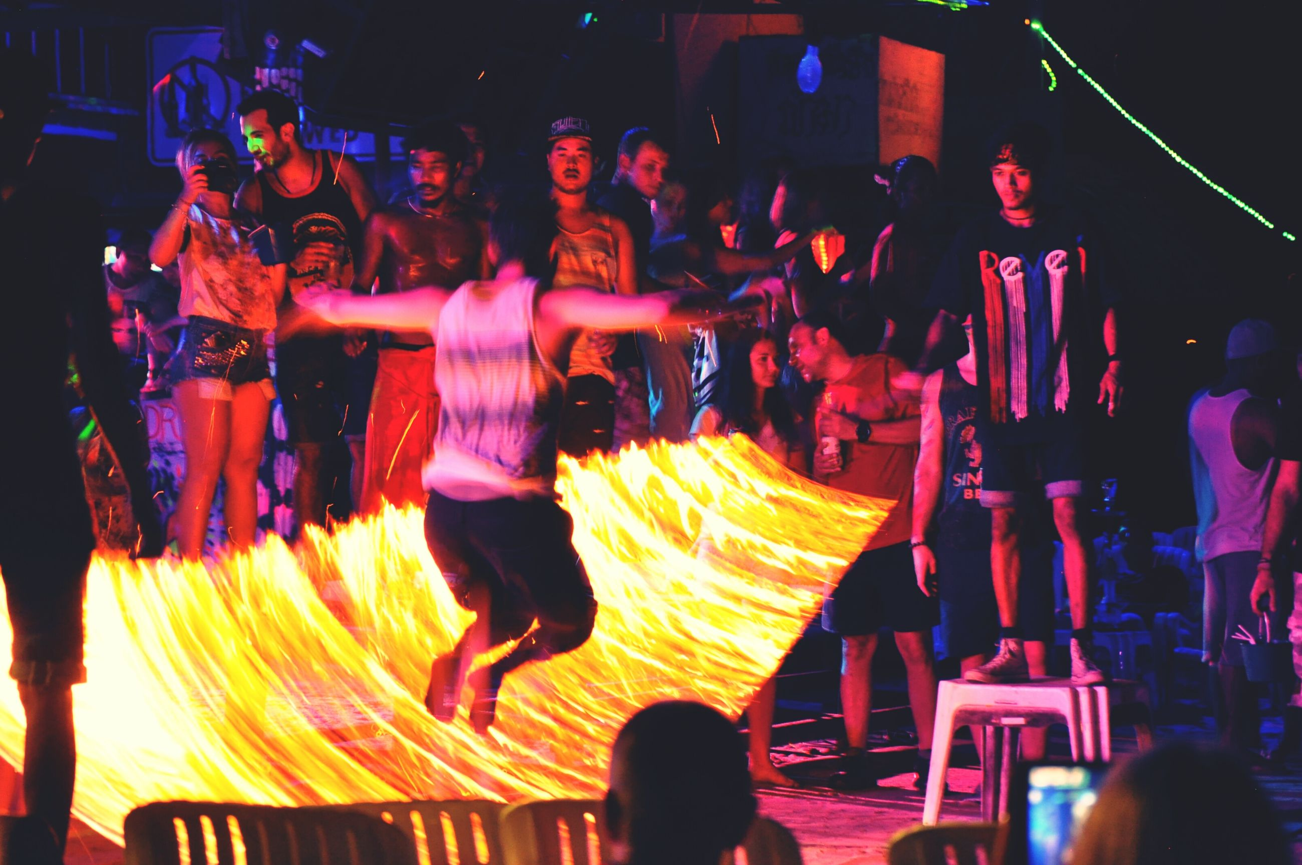 illuminated, men, lifestyles, night, person, large group of people, leisure activity, rear view, crowd, celebration, indoors, standing, arts culture and entertainment, lighting equipment, event, walking, performance, casual clothing, music