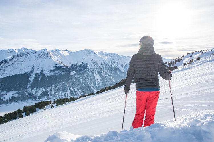 Adventure Beauty In Nature Cold Temperature Day Full Length Healthy Lifestyle Leisure Activity Lifestyles Mountain Nature One Person Outdoors Real People Rear View Scenics Ski Holiday Ski Pole Skiing Sky Snow Sport Vacations Warm Clothing Weather Winter