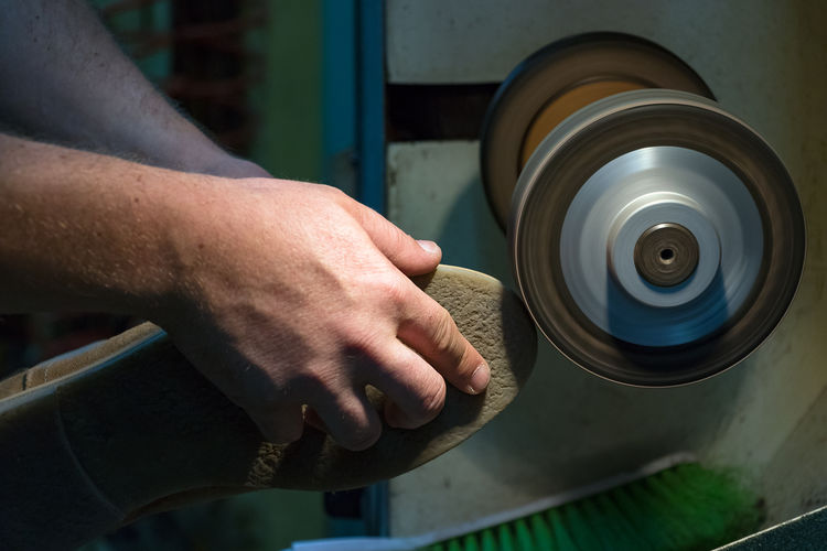 Cropped hands of shoemaker using machinery