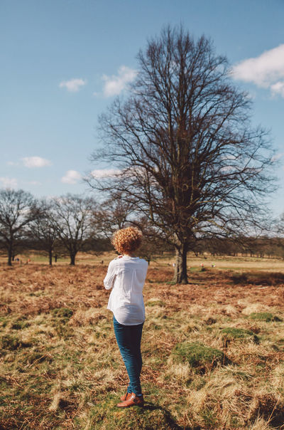 Bare Tree Blue Jeans White Shirt Blue Sky Casual Clothing Childhood Cloud - Sky Field Full Length Girl Grass Happiness Landscape Leisure Activity Lifestyles Nature Rear View Richmond Park, London Sky Standing Tranquil Scene Tranquility Tree Walking 43 Golden Moments People And Places