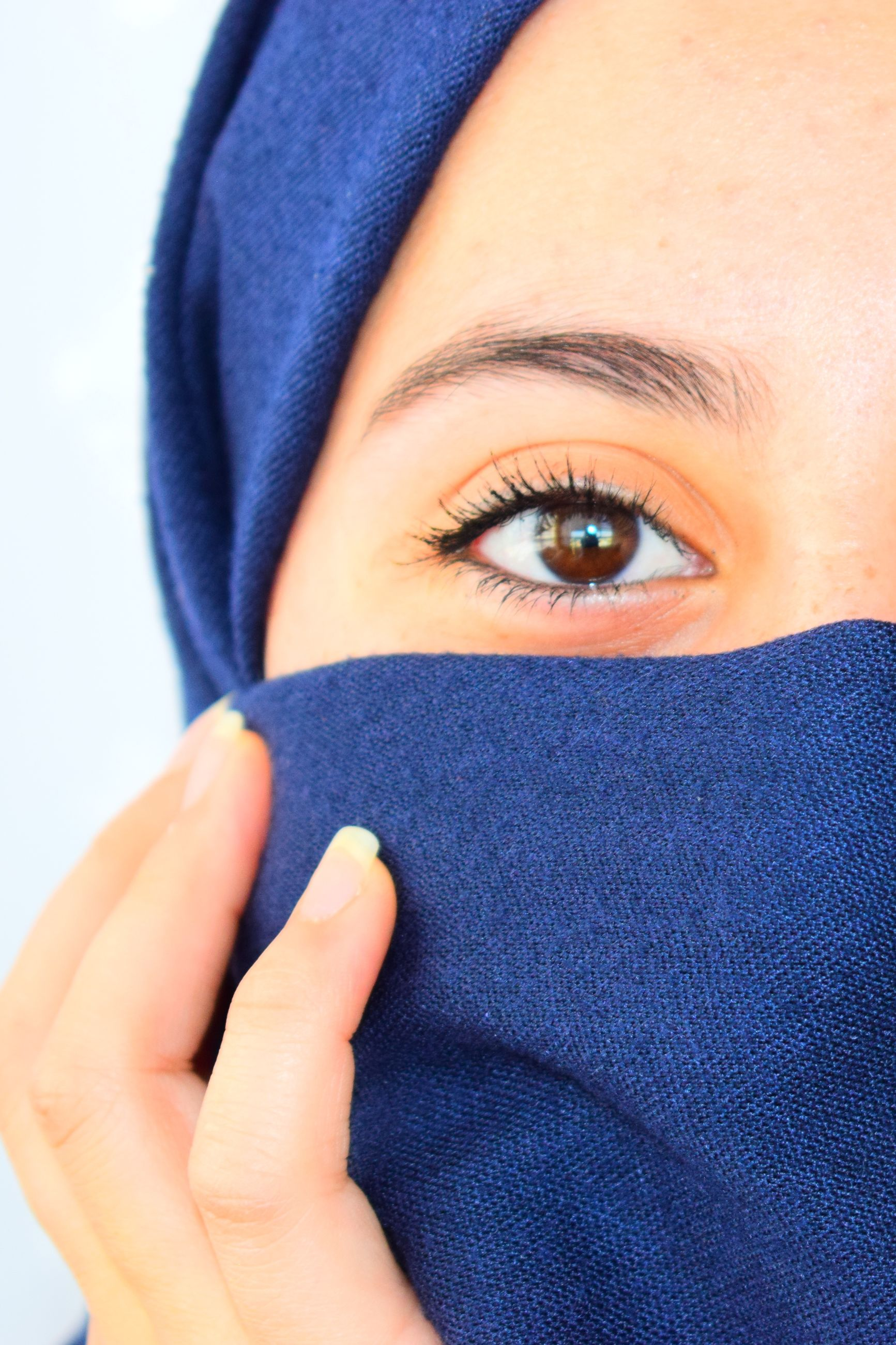human body part, one person, body part, young adult, portrait, human face, headshot, looking at camera, close-up, front view, covering, eye, blue, real people, indoors, clothing, lifestyles, young women, human hand, scarf, obscured face, eyebrow, beautiful woman, warm clothing, purple