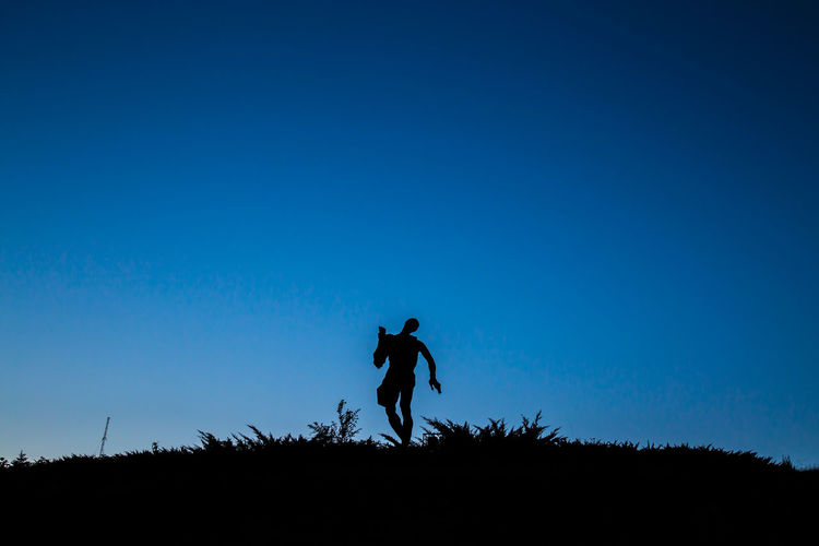 Silhouette Man Standing On Field Against Clear Blue Sky