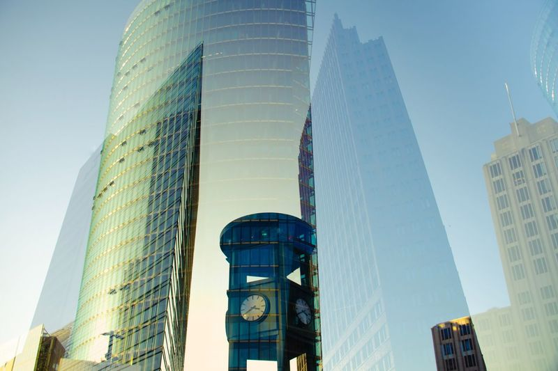 Double exposure of clock tower and modern buildings against clear sky in city