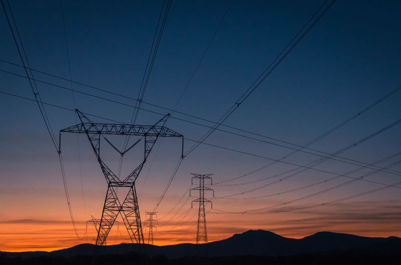 Low angle view of silhouette electricity pylons against sky at sunset