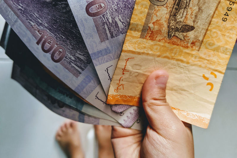Low section of person holding paper currency