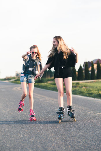 Friends roller skating on road