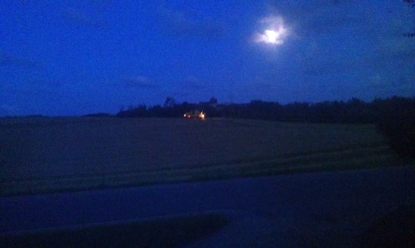 Scenic view of agricultural landscape against sky at night