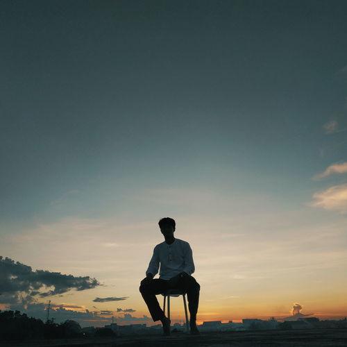 Full length of silhouette man sitting against sky during sunset