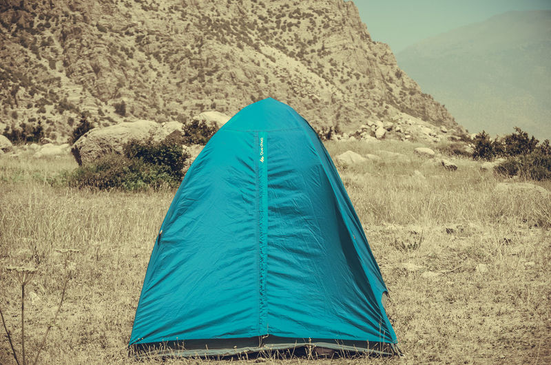 Rear view of tent on field against mountain