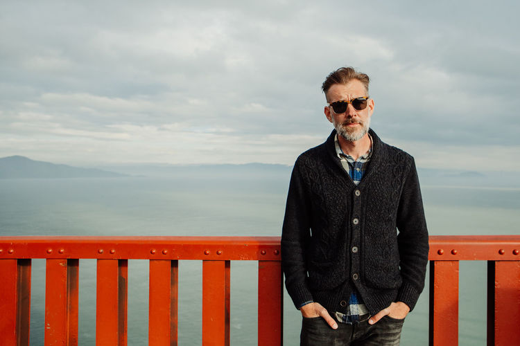 Mature adult male with beard man standing by railing against sea against sky