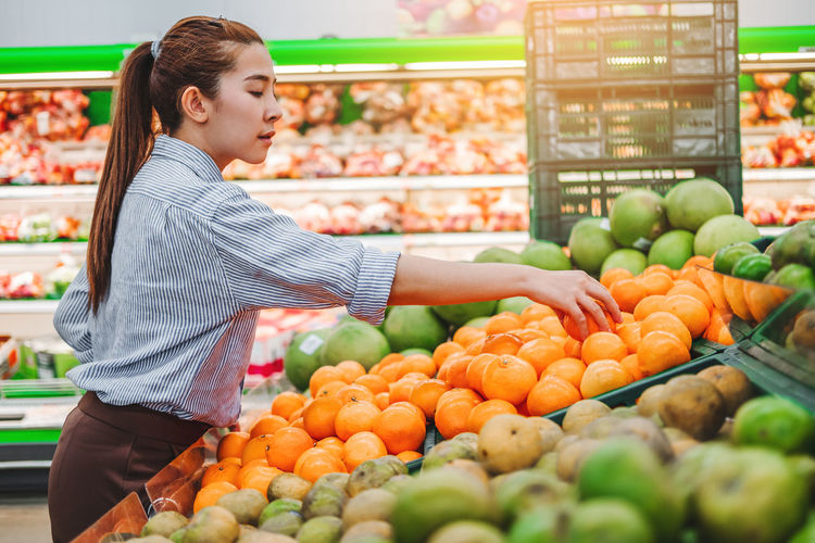 Young woman with vegetables in market