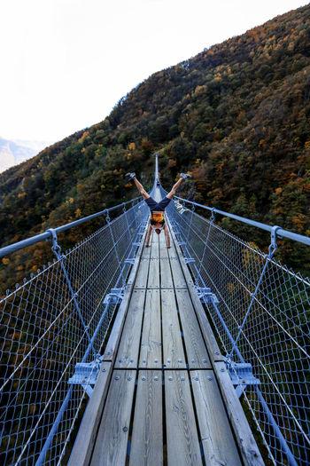 Man Doing Handstand On Footbridge Over Mountain Against Sky