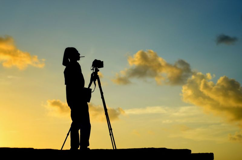 Scenic view of photographer silhoutte on the sunset background. Photography Themes Filming Technology Camera - Photographic Equipment Photographing Standing Full Length Sunset Silhouette Men Camera Photographer Tripod