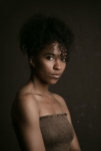 Portrait of woman standing against black background
