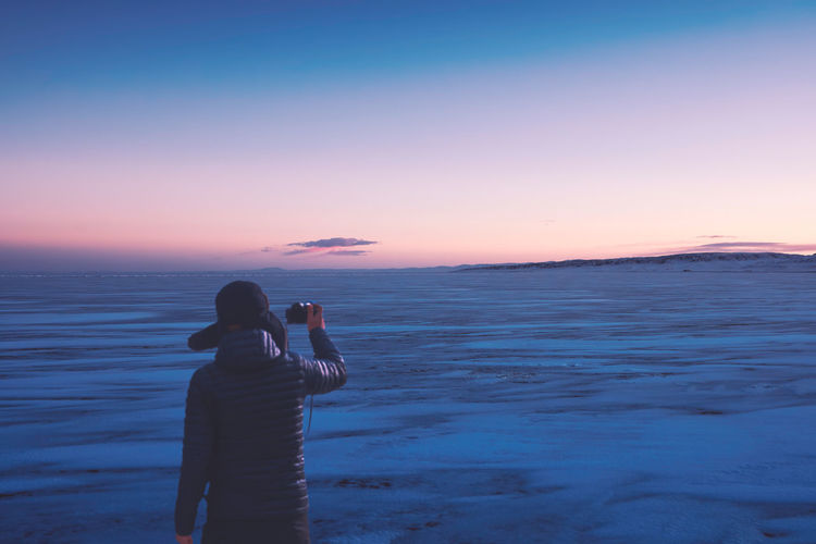 Rear view of men photographing frozen lake against sky during sunset