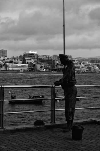 Man standing by river against sky in city