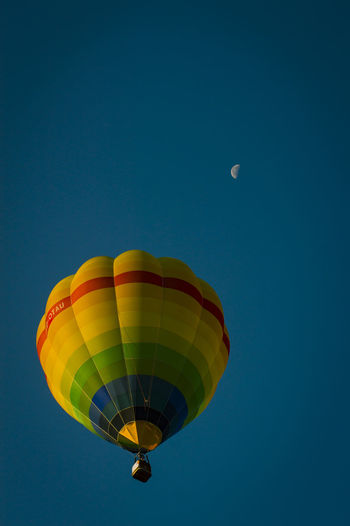 Low angle view of hot air balloon against blue sky and moon