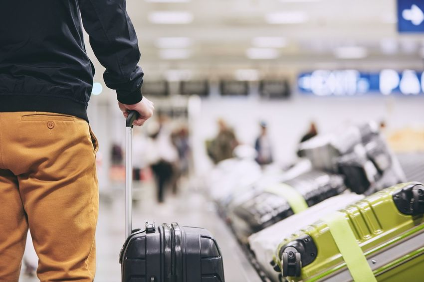 Man traveling by airplane. Young passenger holding his suitcase near baggage claim in airport terminal. Leg Man Passenger Tourist Travel Traveling Trip Vacations Airport Arrival Baggage Baggage Claim Casual Clothing Hand Holding Journey Leaving Lifestyles Limb Luggage People Real People Suitcase Tourism Transportation