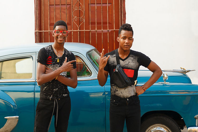 Portrait of young men standing by vintage car in city