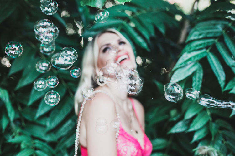 Close-up of bubbles by smiling woman standing against plants