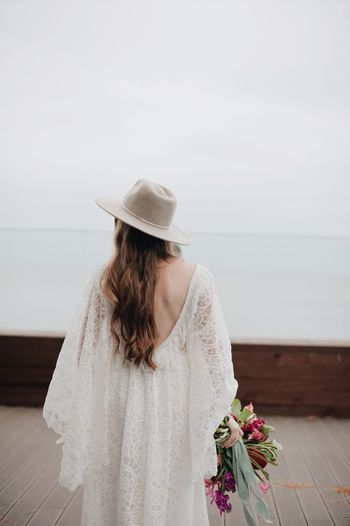Bride Standing On Boardwalk Against Sky