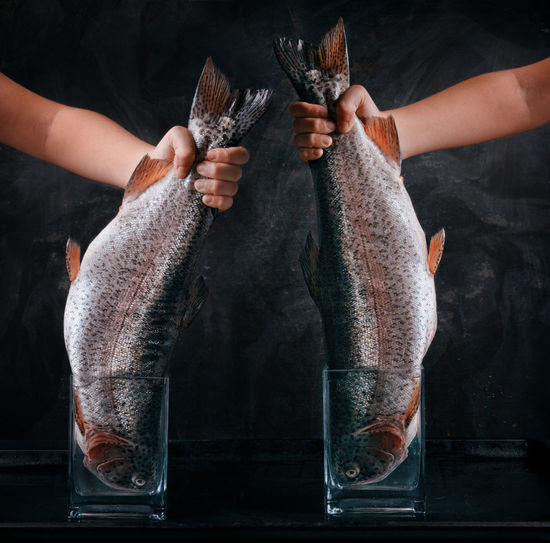 Cropped Hands Holding Fish Against Black Background
