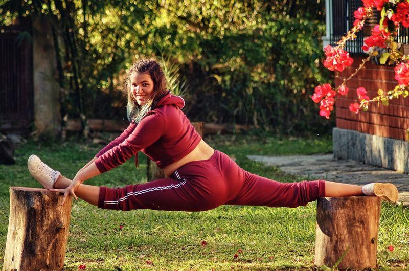 Rear view portrait of teenage girl doing split on tree stumps in yard