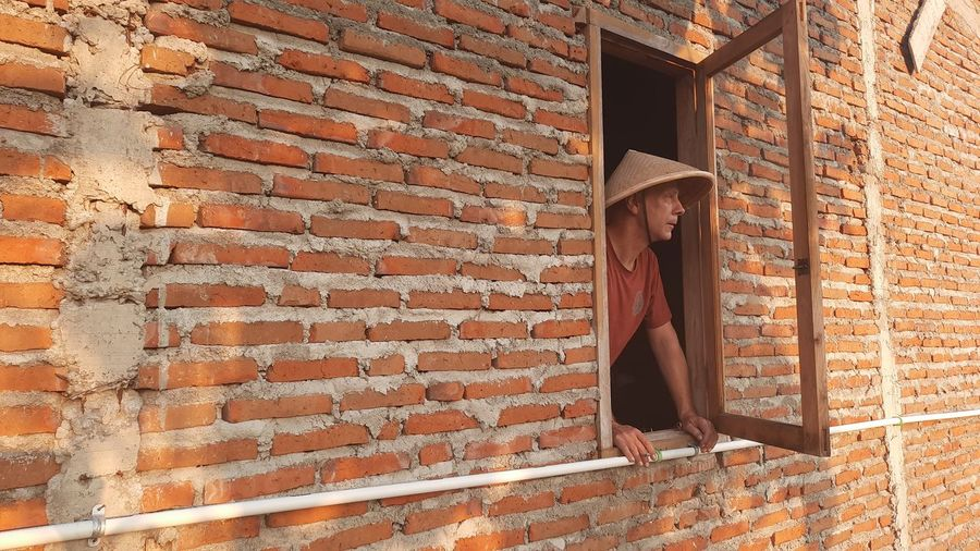 Full length of adult man against brick wall with traditional asian conical hat looking out of window