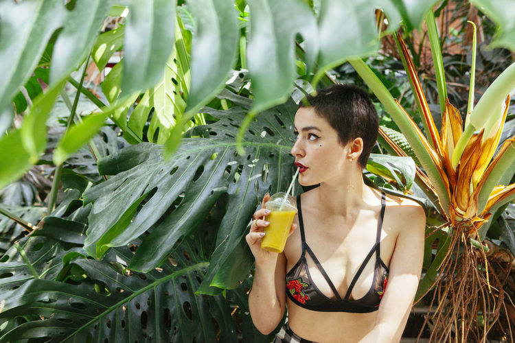 Young woman with short hair drinking juice while sitting against plants