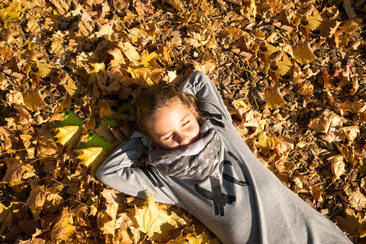 High angle view of girl lying down on leaves during autumn