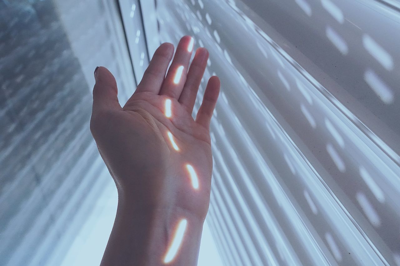 Sunlight falling on hand amidst white walls