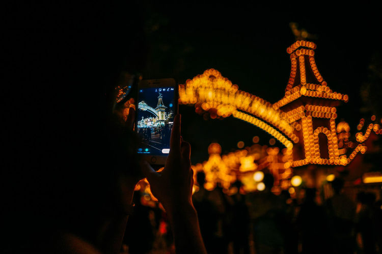 People photographing illuminated building at night