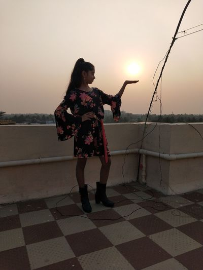 Optical illusion of woman holding sun while standing on terrace