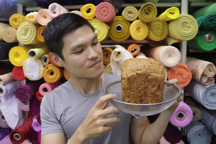 Portrait of young man holding food in colander against multi colored fabric