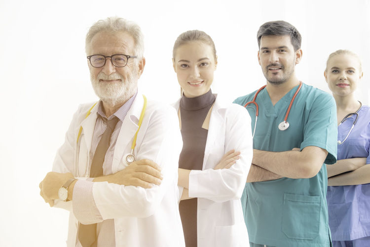 Portrait Of Doctors And Nurse Standing Against White Background