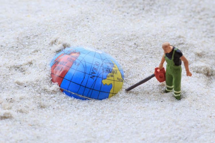 Figurine and globe on sand at beach