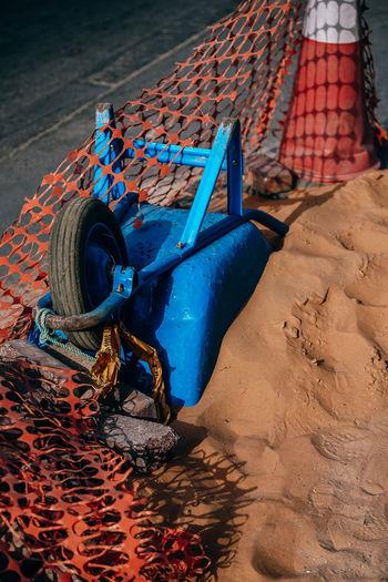 Upside down wheelbarrow on sand