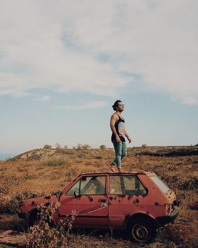 Full length of man standing on abandoned car roof over field against sky