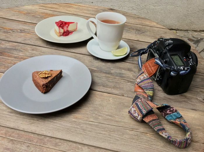 High angle view of cake slices served in plates by tea and camera on table