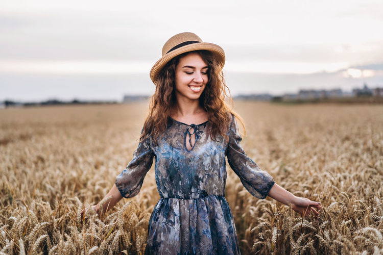 Smiling woman wearing hat standing amidst crops in farm