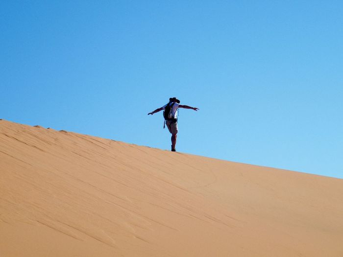 Low angle view of man standing on desert against clear blue sky