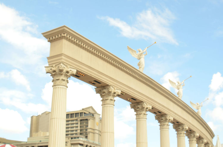 trumpeting angels atop a pillared sconce in Las Vegas in front of the famous Cesar's Palace Angels Angel Wings Architectural Column Architecture Building Exterior Built Structure Cloud - Sky Day History Low Angle View No People Outdoors Sculpture Sky Statue Travel Destinations