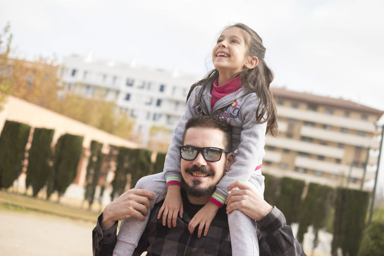 Happy father carrying daughter on shoulder at park
