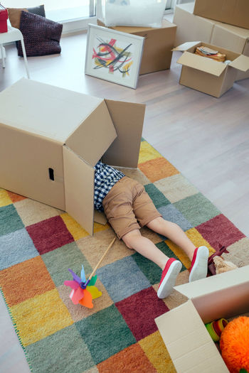 Low section of boy in cardboard box on carpet at home